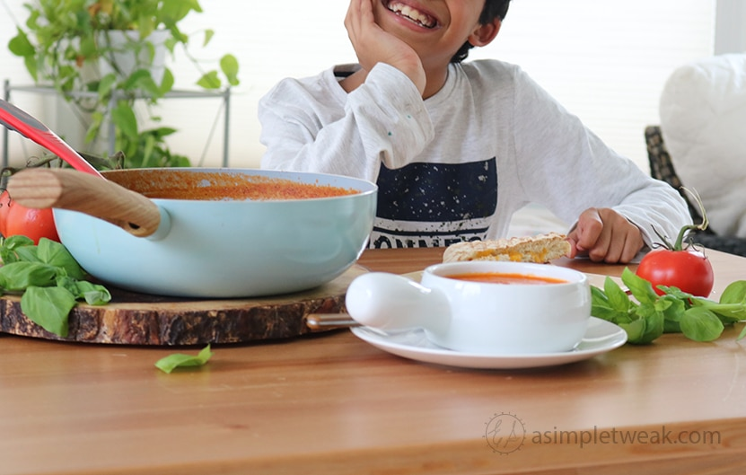 A child smiling in front of a pot and bowl of Creamy Tomato Soup