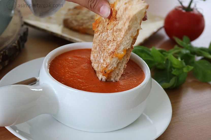 Dipping Grilled Cheese Sandwich in a bowl of Creamy Tomato Soup
