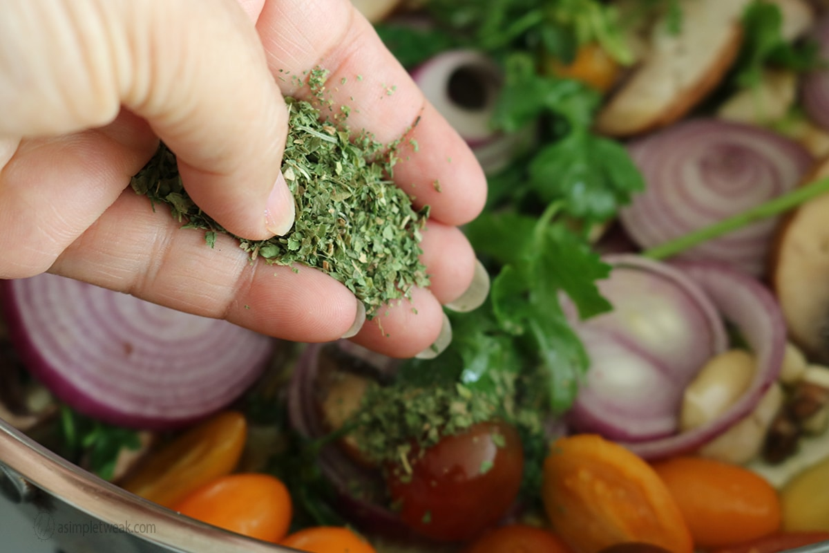 adding dry parsley and oregano to spaghetti