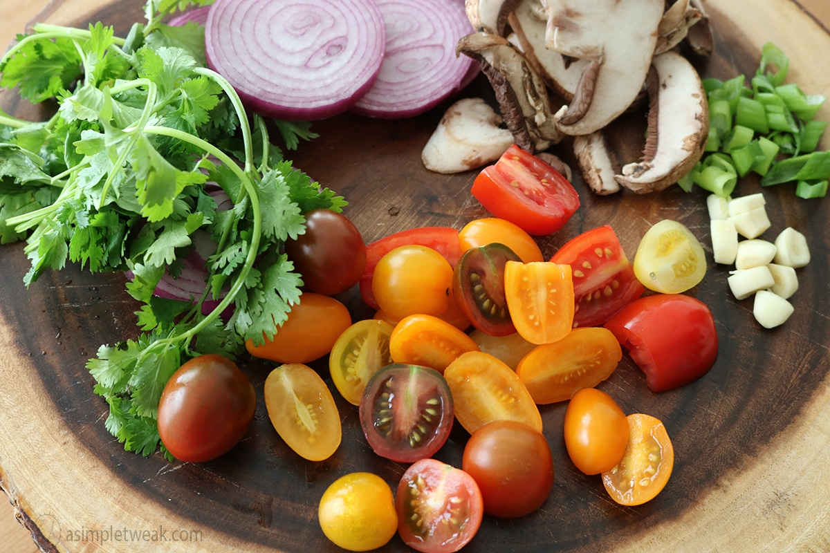 a cutting board with diced tomatoes, cilantro, mushroom, onions, garlic