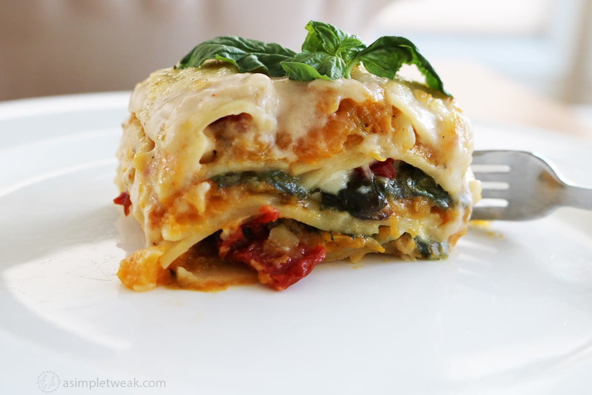 white plate slice of butternut squash lasagna and a fork