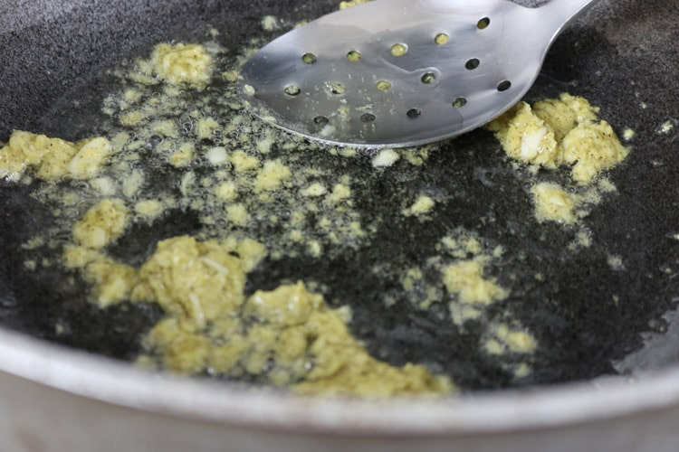 Once you've made the seasoning, place an aluminum pan on the stove at a medium-high temperature. Then, add oil and saute the garlic paste or sofrito.